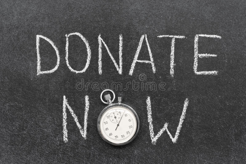 Donate now. Concept handwritten on chalkboard with vintage precise stopwatch used instead of O stock photo