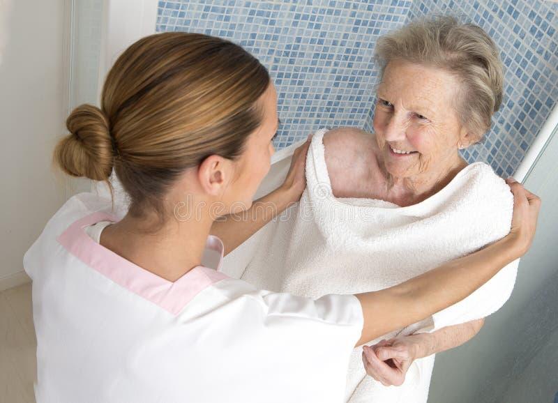 Donateur ou infirmière de soin aidant la femme agée pour la douche photo stock