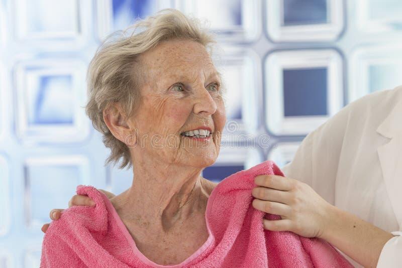 Donateur ou infirmière de soin aidant la femme agée pour la douche photographie stock