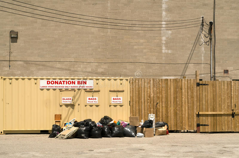 Donation Bins. A large donation bin overfilled and with many bags and such before it royalty free stock photos