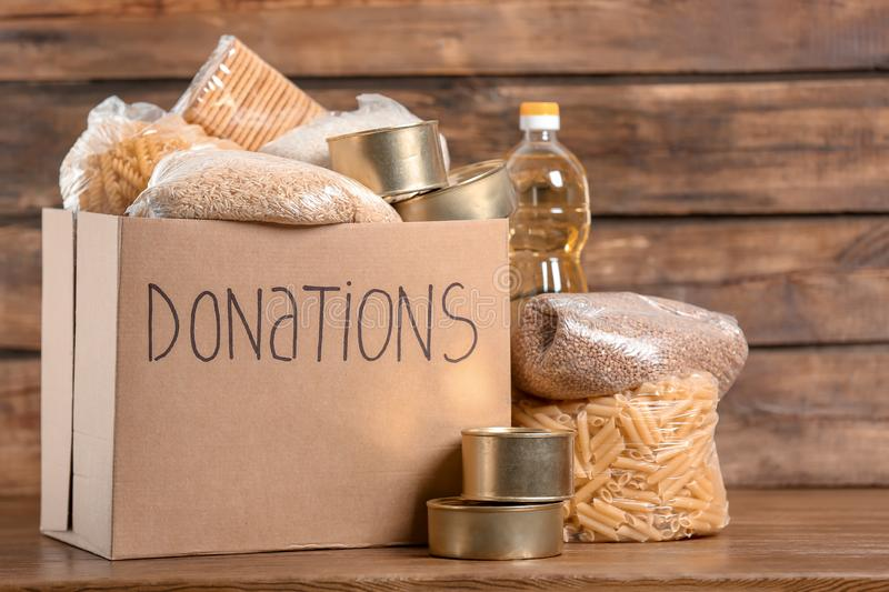 Donation box with food. On wooden background royalty free stock photos