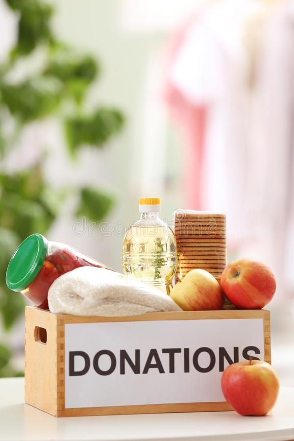 Donation box with food products. On table indoors stock photo