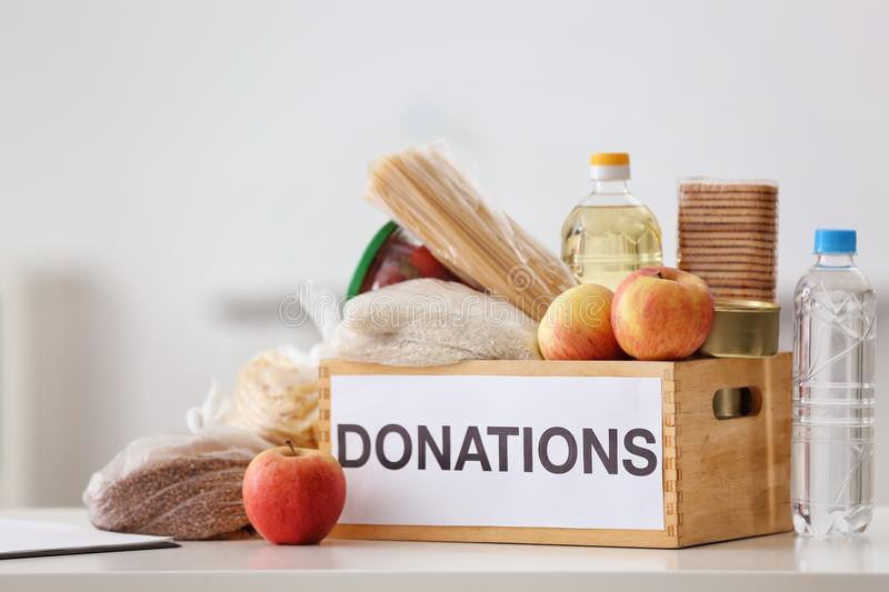 Donation box with food products. On table indoors royalty free stock image
