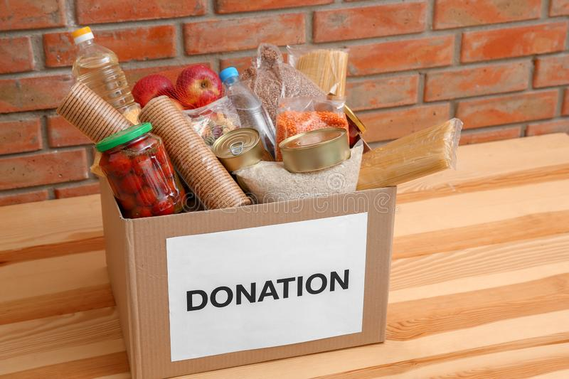 Donation box with food on table near wall royalty free stock photography