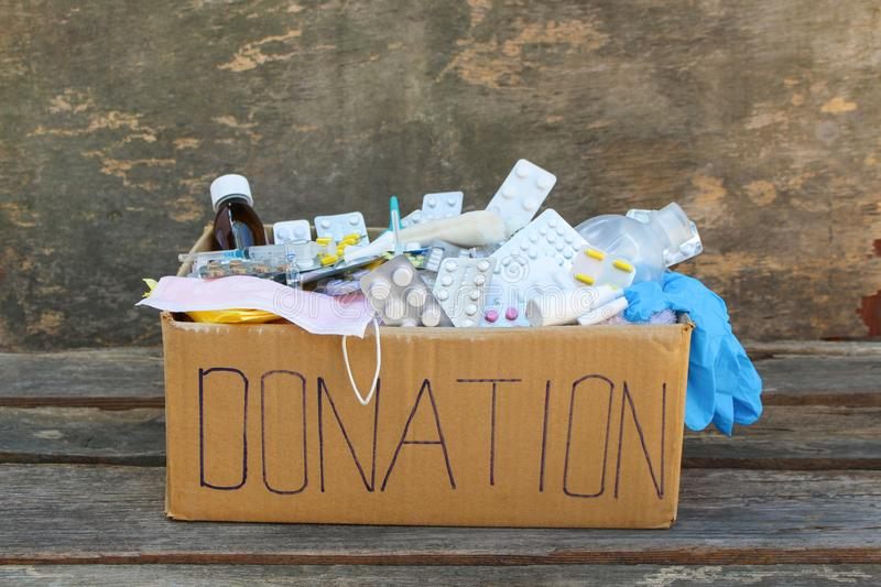 Donation box with medicines. On wooden background stock photography