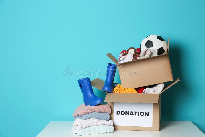 Donation boxes with toys, knitted clothes and shoes on table against color background stock photo
