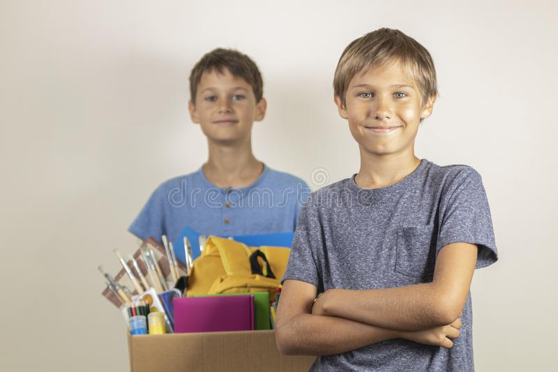 Donation concept. Kids happy to help others. Boys with donation box with books and school supplies royalty free stock photography