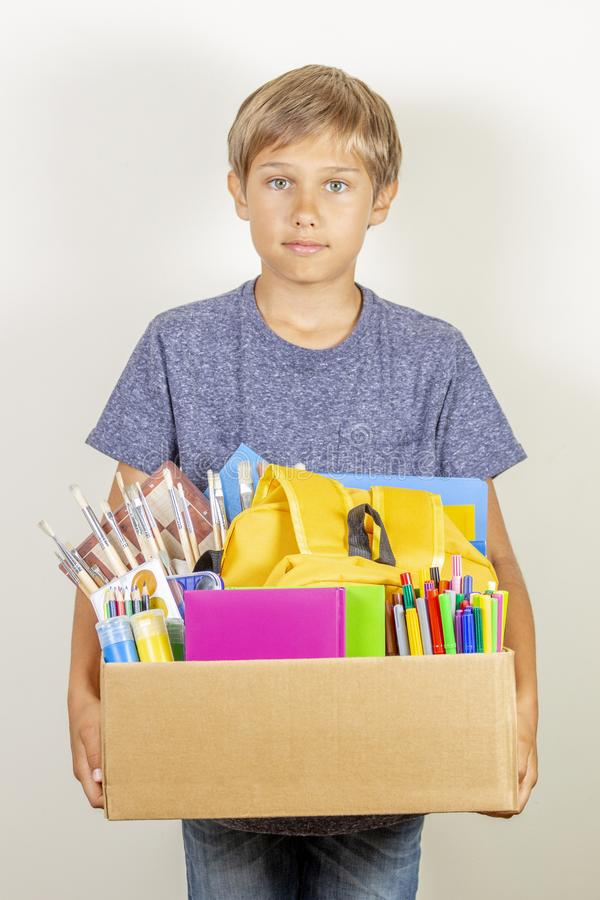 Donation concept. Kid holding donate box with books, pencils and school supplies royalty free stock photo