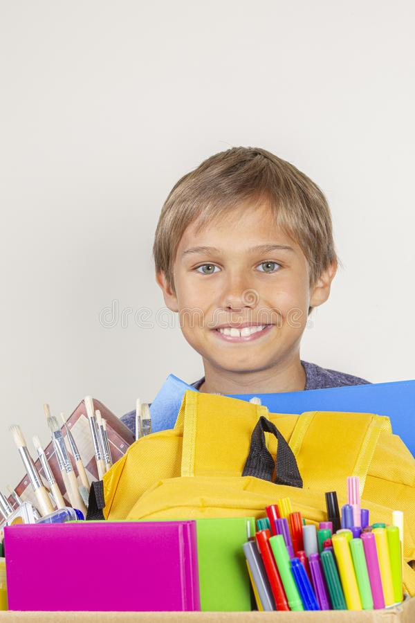 Donation concept. Kid holding donate box with books, pencils and school supplies stock photos