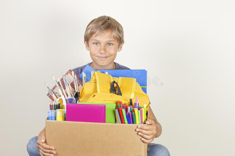Donation concept. Kid holding donate box with books, pencils and school supplies royalty free stock photography