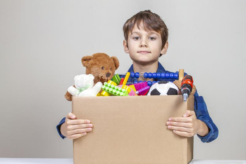 Donation concept. Kid holding donate box with clothes, books, school supplies and toys.  stock photo
