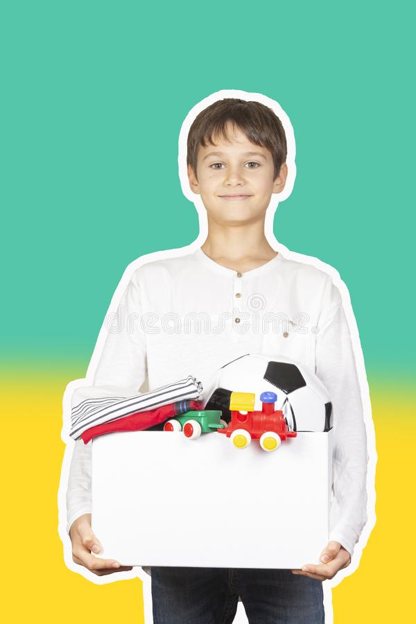 Donation concept. Kid holding donate box with clothes, books, school supplies and toys. Magazine collage style with royalty free stock photos