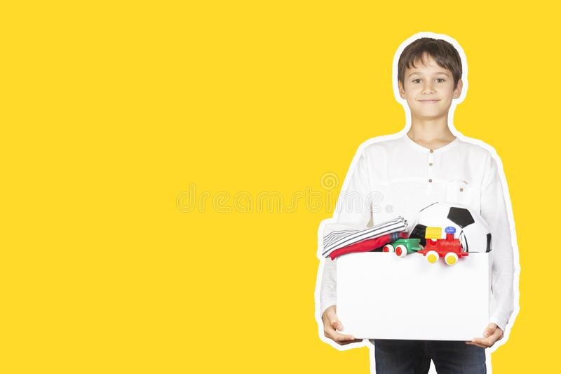 Donation concept. Kid holding donate box with clothes, books, school supplies and toys. Magazine collage style with stock image