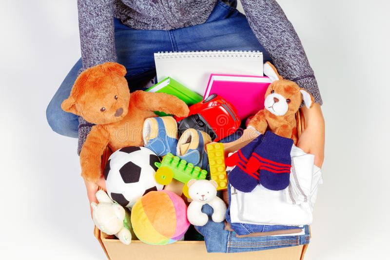 Donation concept. Kid holding donate box with clothes, books, school supplies and toys, white background. Top view stock images