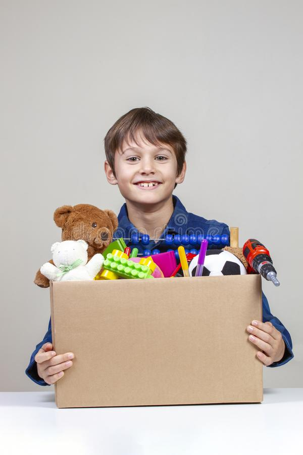 Donation concept. Kid holding donate box with clothes, books and toys.  royalty free stock photography