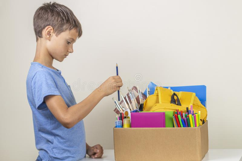 Donation concept. Kid preparing donate box with books, pencils and school supplies for donation royalty free stock photos