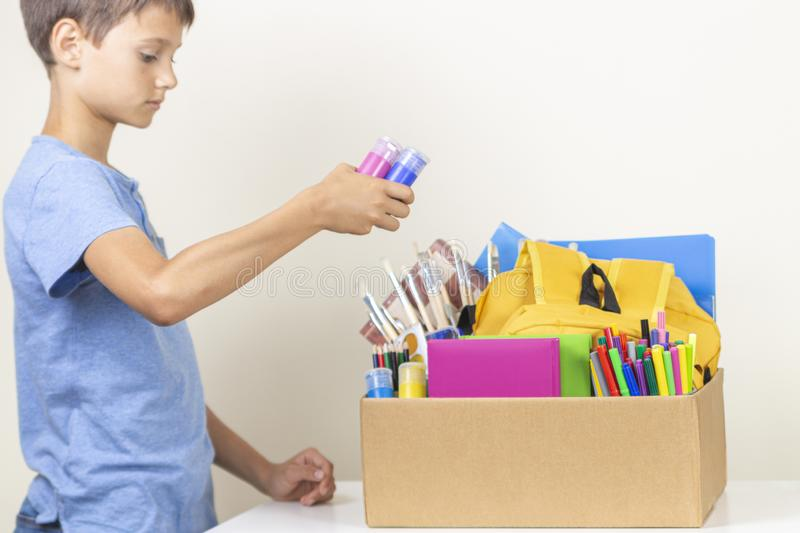 Donation concept. Kid preparing donate box with books, pencils and school supplies for donation royalty free stock images
