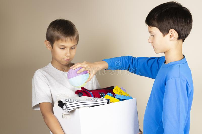 Donation concept. Kids collect donate box. Donation cardboard full of books, clothes and toys.  stock photo