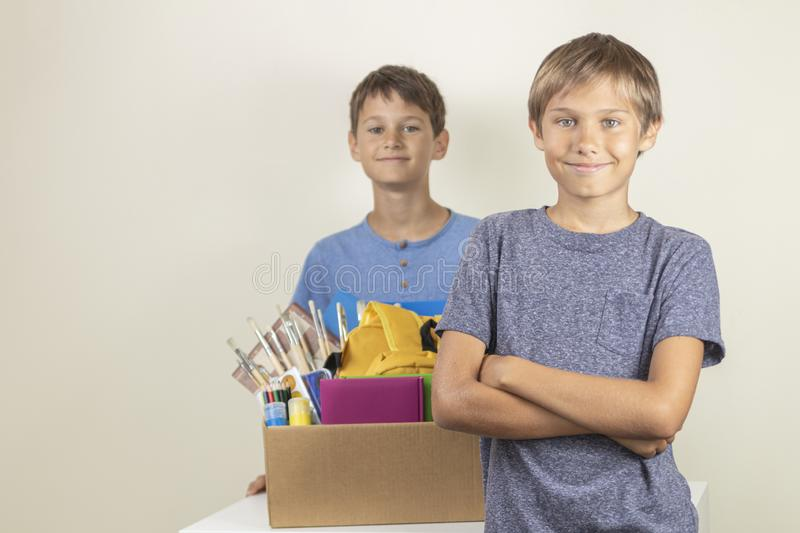 Donation concept. Kids happy to help others. Boys with donation box with books and school supplies royalty free stock images