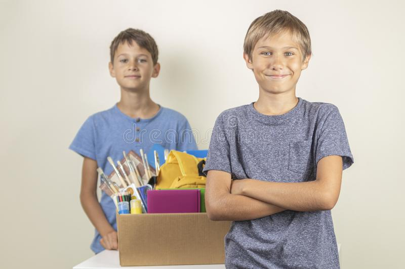 Donation concept. Kids happy to help others. Boys with donation box with books and school supplies royalty free stock photo
