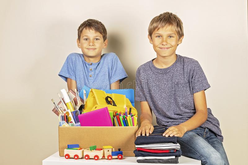 Donation concept. Kids holding donate box with books and school supplies, clothes and toys stock photography