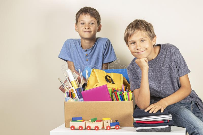 Donation concept. Kids holding donate box with books and school supplies, clothes and toys stock photos
