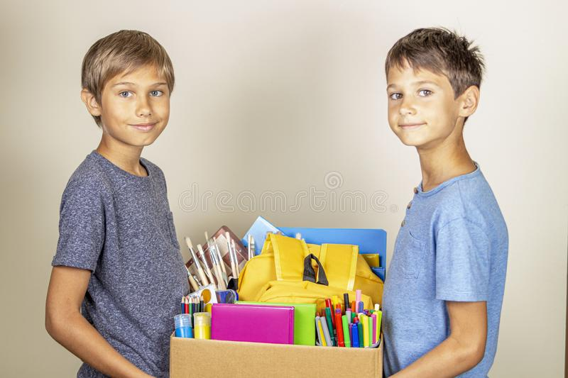 Donation concept. Kids holding donate box with books and school supplies royalty free stock images