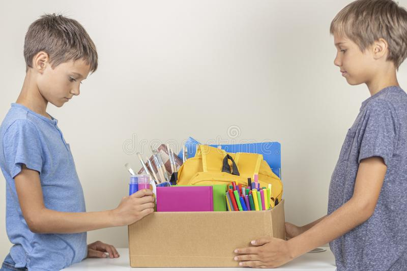 Donation concept. Kids holding donate box with books and school supplies stock photography