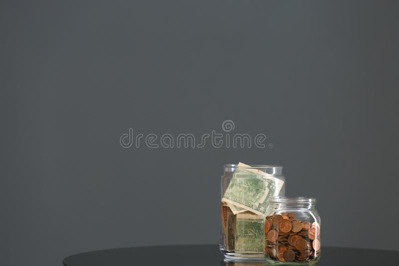 Donation jars with money on table against grey background. Space for text royalty free stock photos