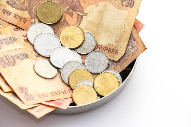 Donation plate with indian banknotes and coins on white background stock photo