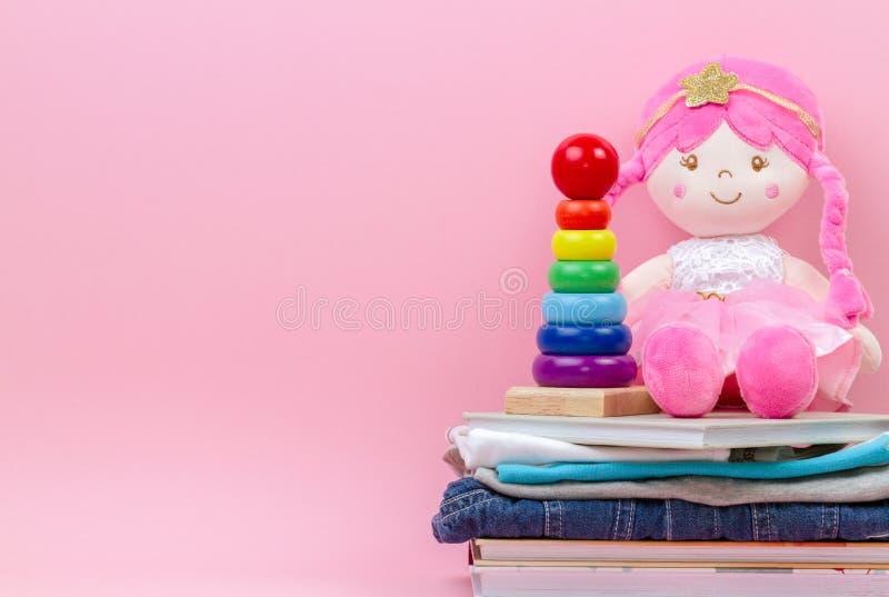 Donation v?lg?renhetbegrepp Den stoppade mjuka dockan, behandla som ett barn stapla cirklar pyramid, ungekl?der och b?cker ?ver r royaltyfri foto
