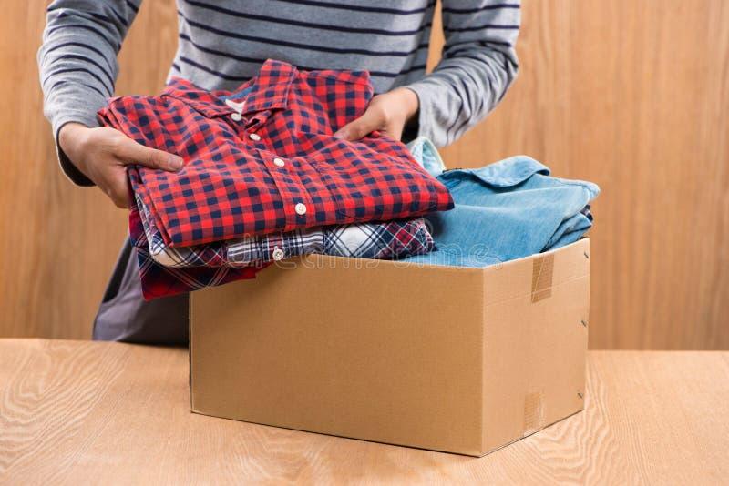 Donationask för fattigt med kläder i manliga händer royaltyfria foton