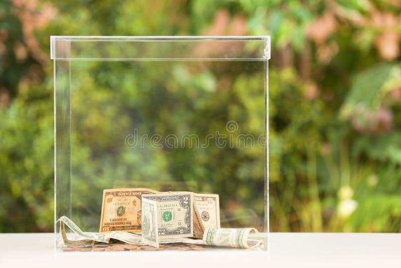 Donationask med pengar på tabellen royaltyfri fotografi