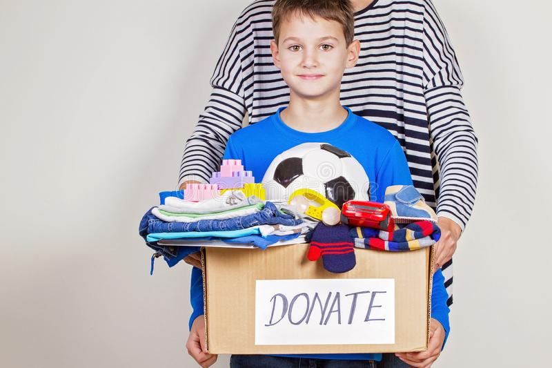 Donationbegrepp Donera asken med kläder, böcker och leksaker i barn och moderhand arkivfoto