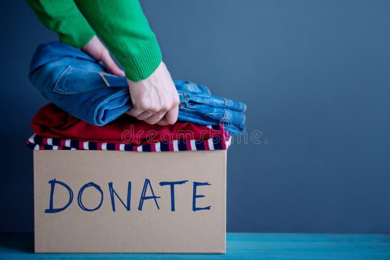Donationbegrepp Kvinnan som förbereder hennes använda gamla kläder in i a, gör arkivbild