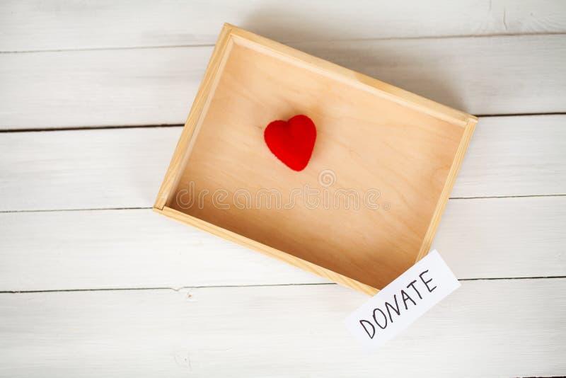 Donationer och välgörenhet Donationbegrepp Ask av donationer och hjärta på den vita bakgrunden arkivfoton