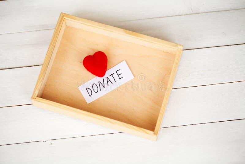 Donationer och v?lg?renhet Donationbegrepp Ask av donationer och hj?rta p? den vita bakgrunden royaltyfria bilder