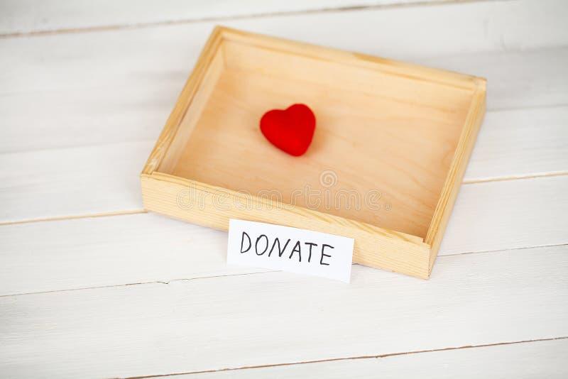 Donationer och v?lg?renhet Donationbegrepp Ask av donationer och hj?rta p? den vita bakgrunden fotografering för bildbyråer