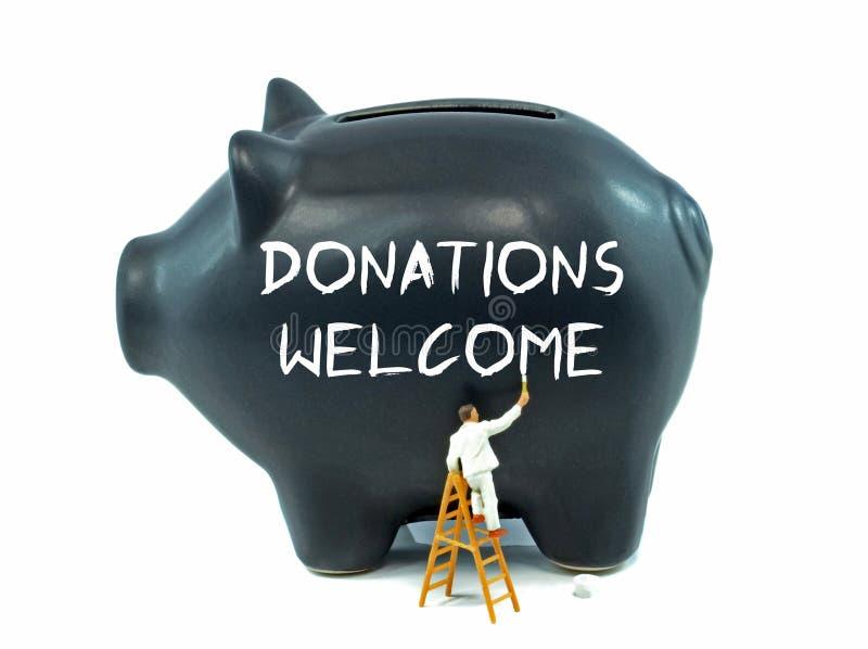 Donationer välkomnar på spargrisen arkivbilder