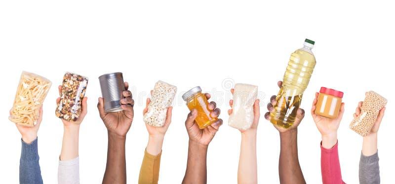 Donations de nourriture dans des mains d'isolement sur le fond blanc image stock
