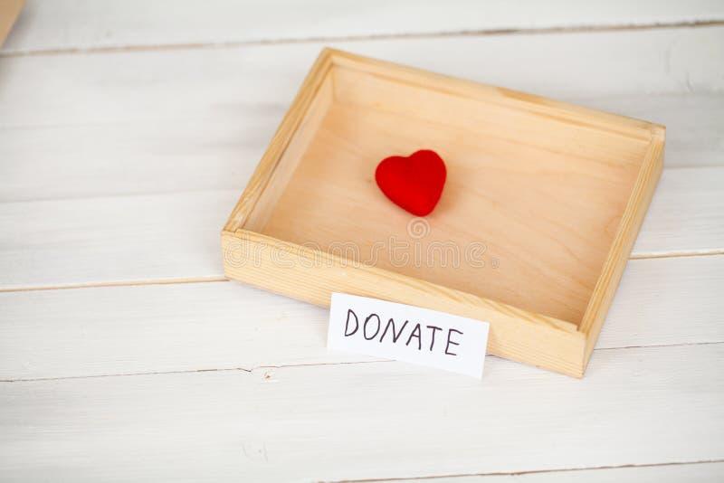 Donazioni e carità Concetto di donazione Scatola delle donazioni e del cuore sui precedenti bianchi immagini stock