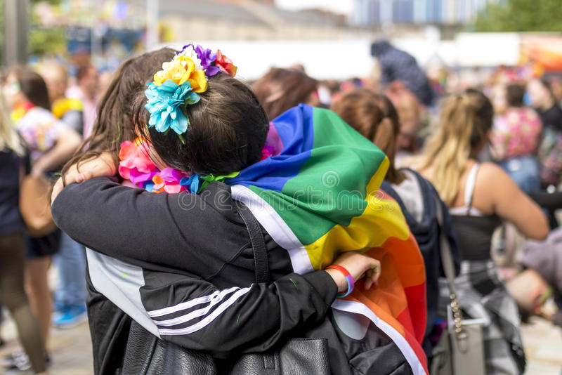 Doncaster Pride 19 Aug 2017 LGBT Festival. Couple hug with flag drapered over shoulders royalty free stock images