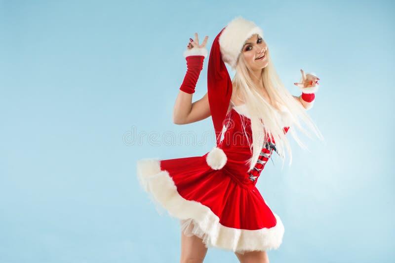 Doncella de la nieve del baile Mujer rubia encantadora y atractiva en un traje de Papá Noel fotos de archivo