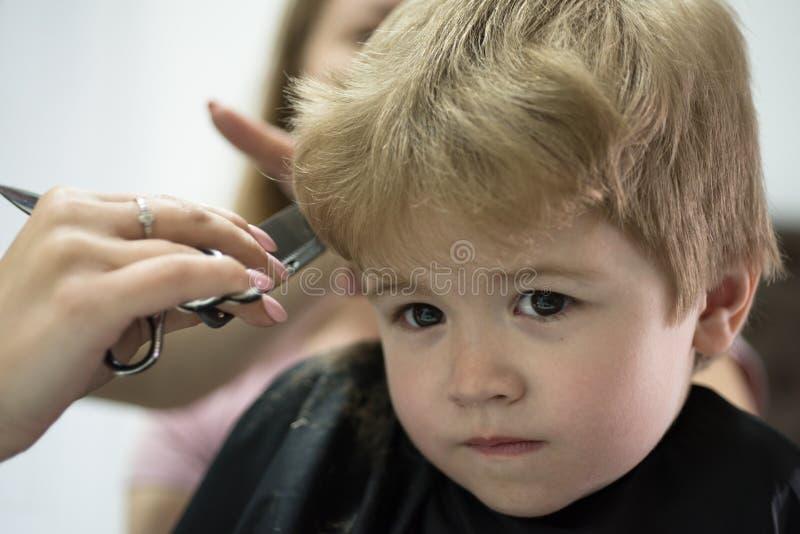 Donde está juego el corte de pelo de los childs Pequeño niño en salón de la peluquería Corte de pelo dado del pequeño niño Niño p fotografía de archivo