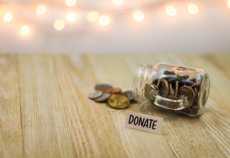 Done el concepto del dinero con las monedas brillantes en un tarro de cristal fotos de archivo libres de regalías