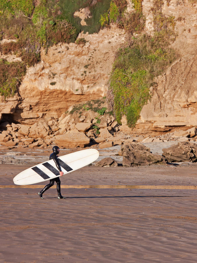 Done Surfing. SAUNTON SANDS, ENGLAND - DECEMBER 3, 2014: Surfer leaving the sea at the end of the day. The bay in North Devon is popular with surfers and stock images