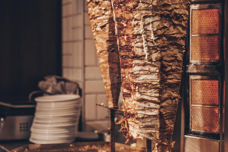 Doner kebab - dish in Middle Eastern cuisine. Roasted meat for shawarma in the street cafe or restaurant. royalty free stock photo