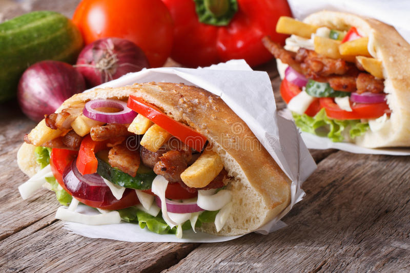 Doner kebab with meat and vegetables in pita wrapped in paper royalty free stock image