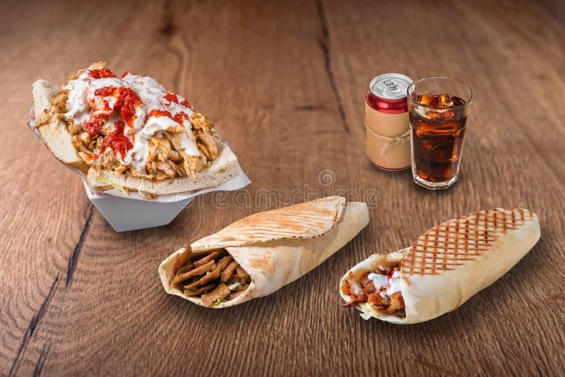 Doner kebab, pita kanapki i kola na drewnianym tle, fotografia royalty free