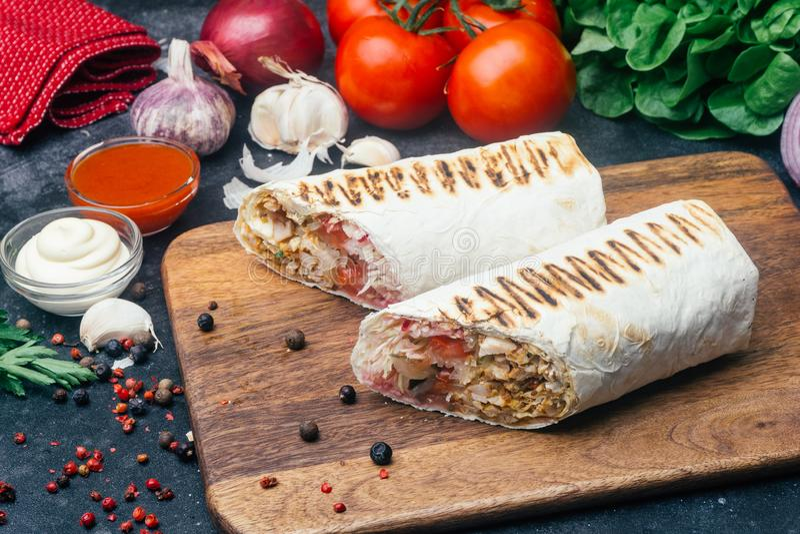 Doner kebab shawarma或doner套 在lavash皮塔饼面包的烤鸡与新鲜蔬菜-蕃茄,蔬菜沙拉, 免版税库存图片